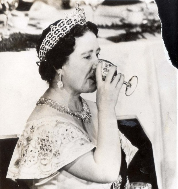 The Queen Mother Elizabeth in a classic pose as she sips on a glass of wine.